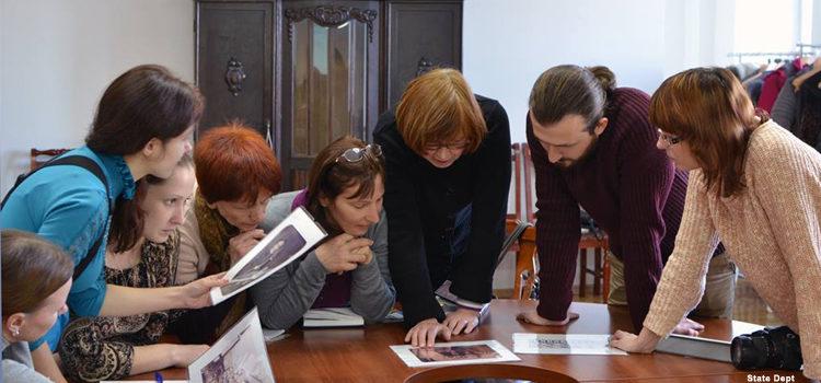 Группа людей за столом рассматривает задание (Фото Госдепартамента США)