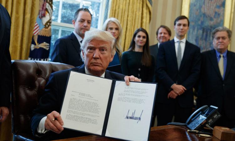 Президент Трамп демонстрирует свою подпись под административным указом (AP Photo/Evan Vucci)