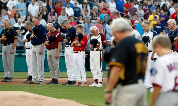 Members of both teams bow their heads for a moment of silence for Representative Steve Scalise before the Congressional Baseball Game on June 15 in Washington. (© AP Images)