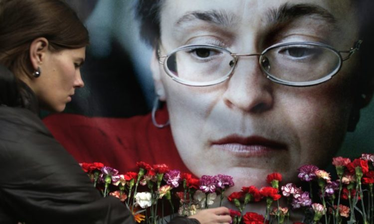 A woman places flowers before a portrait of slain Russian journalist Anna Politkovskaya, in Moscow. AP Photo